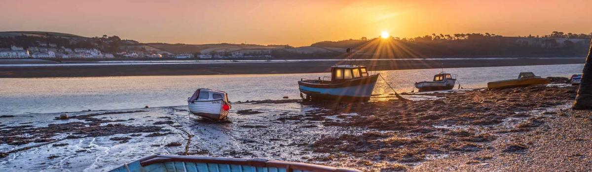 Small boats on the estuary as the sun rises above Westerliegh